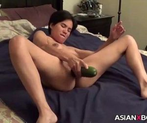 Asian MILF inserts a cucumber